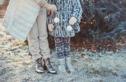 幸福家庭的画象:有她的走在冬天城市公园的小逗人喜爱的女儿的一年轻美女 库存照片