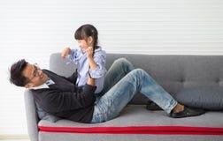 幸福家庭逗人喜爱的女孩女儿和父亲是拥抱,并且使用在沙发在客厅在家度过时间假日 免版税库存照片