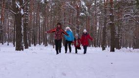 幸福家庭通过多雪的杉木公园和笑跑 与他们的父母的儿童游戏在冬天森林和微笑里 股票视频
