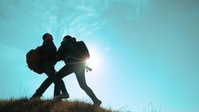 幸福家庭配合帮助商务旅游概念 两个徒步旅行者人和妇女游人登山人在上面上升 股票录像