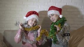 幸福家庭,两个姐妹,使用与五颜六色的闪亮金属片的圣诞老人的帽子的,并且跳舞坐长沙发反对白色 股票录像