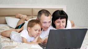 幸福家庭:爸爸、妈妈和婴孩在床上说谎并且使用膝上型计算机,微笑 影视素材