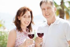 幸福家庭-摆在,与红酒的男人和妇女在暑假海滩背景中 免版税库存图片