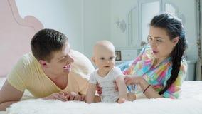 幸福家庭-母亲、父亲和婴孩在床上早晨 股票录像