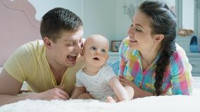 幸福家庭-母亲、父亲和婴孩在床上 股票视频