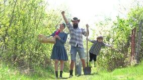 幸福家庭-激动的农夫概念 种植在地面eco生活概念的国家人生的人 母亲父亲和儿子 股票录像