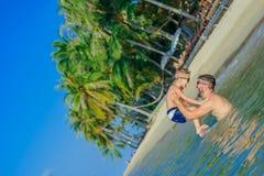 幸福画象在热带水中:有胡子的父亲投掷他的 免版税库存照片
