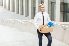 幸福经理有一个新的工作 穿着体面的红色头发年轻成人工作者,去新的更好的工作 在台阶的室外射击,移动 免版税库存照片