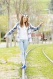 幸福美丽的行家女孩在街道的老路轨走 库存图片