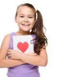 幸福-有红色心脏的微笑的女孩 免版税库存照片