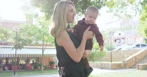 幸运母亲在手上跑与婴孩在背景公园 股票录像