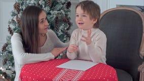 幻想怎样的一个愉快的男孩和他的母亲在信件中写道给圣诞老人 图库摄影