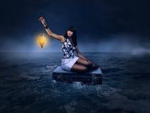 幻想概念 美丽的妇女坐单独一个手提箱在海 库存照片