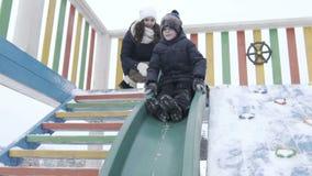 幻灯片 冬天公园,儿童` s操场 slidding的男孩下来 股票视频