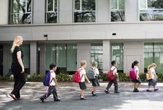 幼儿园学生走的横穿学校路 免版税库存照片