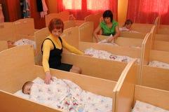 幼儿园教育家放置下午休息的孩子 免版税库存图片