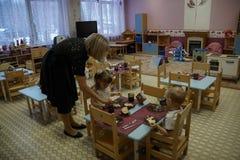 幼儿园老师帮助孩子吃 吃早餐的小男孩和女孩在幼儿园 库存图片