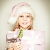 幼儿女孩在有圣诞节礼物的圣诞老人帽子穿戴了 免版税图库摄影
