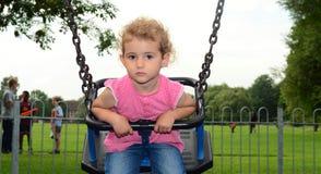幼儿,女孩,使用在摇摆在操场。 免版税库存图片