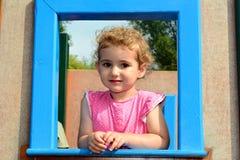 幼儿,女孩,看通过框架 免版税库存图片