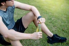 幼小亚洲人赛跑者饮用的能量饮料在跑在Th以后 库存图片