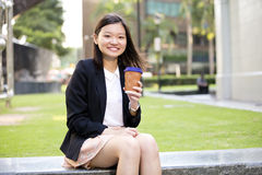 幼小亚洲女性执行委员饮用的咖啡和使用膝上型计算机个人计算机 库存照片