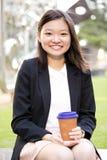幼小亚洲女性执行委员饮用的咖啡和使用膝上型计算机个人计算机 免版税库存图片