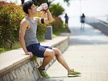 幼小亚洲慢跑者休息的和饮用水 库存照片