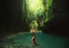 幼小和性感的若虫在峡谷走 停留在阳光下光 使用用绿松石水 wearig长 图库摄影