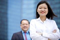 幼小女性亚洲执行委员和资深亚洲商人微笑的画象 免版税图库摄影