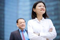 幼小女性亚洲执行委员和资深亚洲商人微笑的画象 免版税库存图片