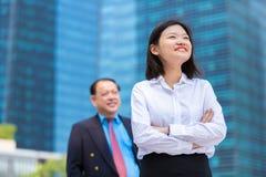 幼小女性亚洲执行委员和资深亚洲商人微笑的画象 免版税库存照片