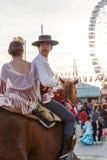 幼小男孩和女孩骑乘马和穿戴在庆祝塞维利亚` s 4月市场的传统服装 库存照片