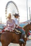 幼小男孩和女孩骑乘马和穿戴在庆祝塞维利亚` s 4月市场的传统服装 图库摄影