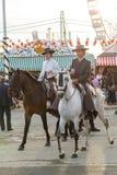 幼小男孩和女孩骑乘马和穿戴在庆祝塞维利亚` s 4月市场的传统服装 库存图片