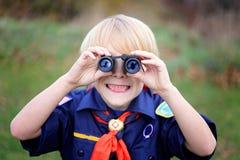 幼小虎犊侦察微笑对照相机通过双筒望远镜 免版税库存图片
