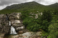 幽谷Coe,苏格兰,与山和云彩的瀑布在背景中 免版税库存图片