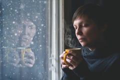 幽静妇女饮用的咖啡在暗室 免版税库存图片