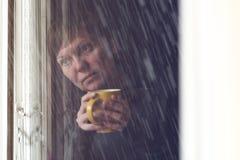 幽静妇女饮用的咖啡在暗室 库存照片