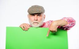 广告商店 在横幅地方公告外面的资深有胡子的人偷看 领抚恤金者祖父在葡萄酒帽子举行 库存图片