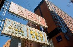 广告广告牌的霓虹灯在香港摩天大楼墙壁上的  免版税库存照片