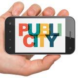 广告概念:拿着有宣传的手智能手机在显示 免版税库存图片