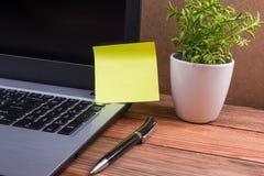 广告的黄色空白的笔记在计算机个人计算机屏幕,办公桌桌上有suplies木难看的东西葡萄酒背景 库存照片
