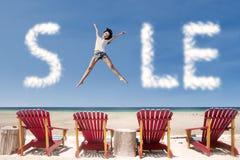 广告销售云彩和女孩跳过海滩睡椅 免版税库存图片