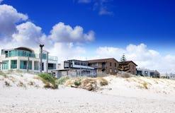 广场家和俯视美丽的白色沙滩的街道房子 免版税库存照片