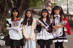 广州,中国- 2016年3月15日:四个中国微笑的俏丽的学生女孩在学校佩带与花 库存照片