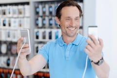广泛咧嘴成人的顾客,当购物智能手机时 免版税库存图片