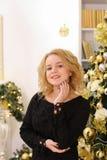 广泛微笑和摆在反对圣诞节tre的愉快的白肤金发的女孩 免版税库存照片