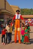 广泛微笑,当摆在与孩子在Ramoji影片城市-世界` s最大的电影厂复合体时的高跷的友好的小丑 库存图片
