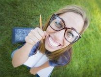 广角书痴青少年的佩带的镜片拿着铅笔 免版税库存照片